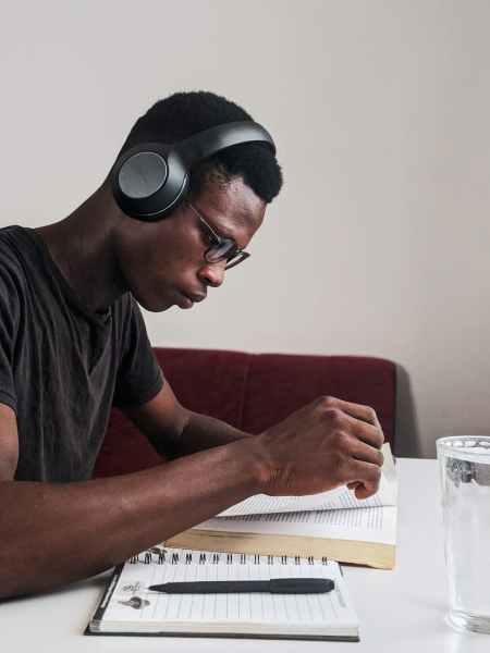 man wearing black crew neck t shirt using black headphones reading book while sitting